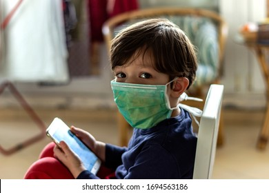 Young boy,while in quarantine at is own home,play on smartphone.Caucasian sad little child looking at mobile,using surgical mask.Boy wearing respiratory mask as prevention against Coronavirus Covid-19