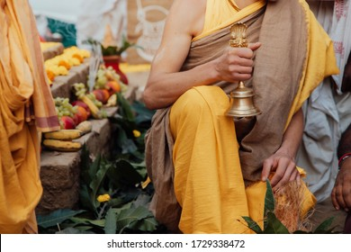 young Brahman Brahmachari holds a bell in his hands during Yagya a fire flame ritual of hindu pooja performating during sacred traditional Vedic ceremony. - Shutterstock ID 1729338472