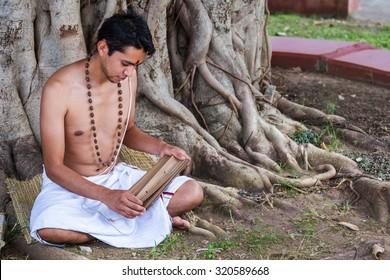 A young brahmin reads an ancient Hindu text under a banyan tree.  - Shutterstock ID 320589668