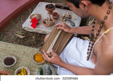 A young brahmin reads an ancient Hindu text surrounded by natural medicinal ingredients.  - Shutterstock ID 320589686