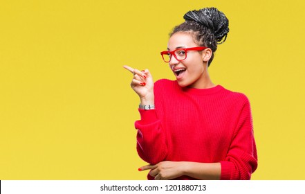 6f64a0da171 Young braided hair african american girl wearing sweater and glasses over  isolated background with a big