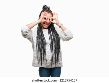 Young braided hair african american girl wearing sweater over isolated background doing ok gesture like binoculars sticking tongue out, eyes looking through fingers. Crazy expression.