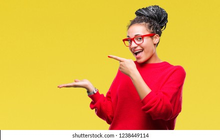 Young braided hair african american girl wearing sweater and glasses over isolated background amazed and smiling to the camera while presenting with hand and pointing with finger.