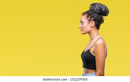 Young braided hair african american with pigmentation blemish birth mark over isolated background looking to side, relax profile pose with natural face with confident smile.