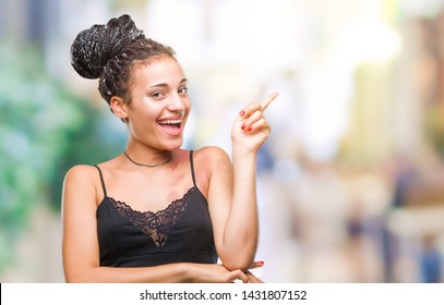 Young braided hair african american with pigmentation blemish birth mark over isolated background with a big smile on face, pointing with hand and finger to the side looking at the camera.
