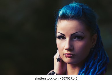 Young braided punk girl posing.Portrait of cool freaky white chick with lie piercing on face,dyed blue braided hair.Hairstyle model with braids & make up.Street fashion female model