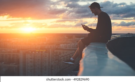 Young brave man sitting on the edge of the roof with smartphone at sunset