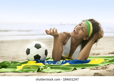 young Brazil supporter on beach in team colors with football