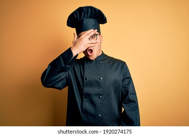 Young brazilian chef man wearing cooker uniform and hat over isolated yellow background peeking in shock covering face and eyes with hand, looking through fingers with embarrassed expression.