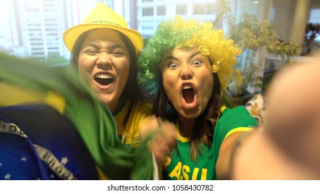 Young Brazilian friends celebrating during soccer match at home