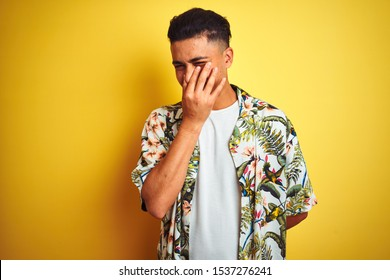 Young brazilian man on vacation wearing summer floral shirt over isolated yellow background smelling something stinky and disgusting, intolerable smell, holding breath with fingers on nose. Bad smells