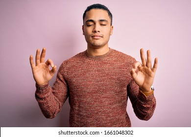 Young brazilian man wearing casual sweater standing over isolated pink background relax and smiling with eyes closed doing meditation gesture with fingers. Yoga concept.