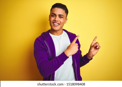 Young brazilian man wearing purple sweatshirt standing over isolated yellow background smiling and looking at the camera pointing with two hands and fingers to the side.