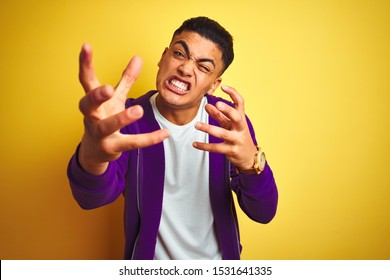 Young brazilian man wearing purple sweatshirt standing over isolated yellow background Shouting frustrated with rage, hands trying to strangle, yelling mad