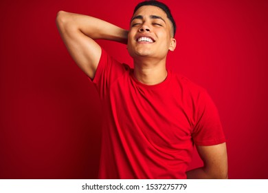 Young brazilian man wearing t-shirt standing over isolated red background smiling confident touching hair with hand up gesture, posing attractive and fashionable
