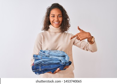 Young brazilian shopkeeper woman holding pile of jeans over isolated white background very happy pointing with hand and finger