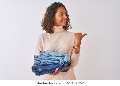 Young brazilian shopkeeper woman holding pile of jeans over isolated white background pointing and showing with thumb up to the side with happy face smiling