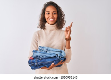 Young brazilian shopkeeper woman holding pile of jeans over isolated white background surprised with an idea or question pointing finger with happy face, number one