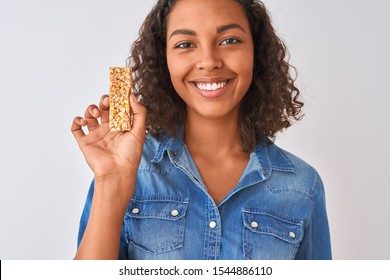 Young brazilian woman eating granola bar standing over isolated white background with a happy face standing and smiling with a confident smile showing teeth