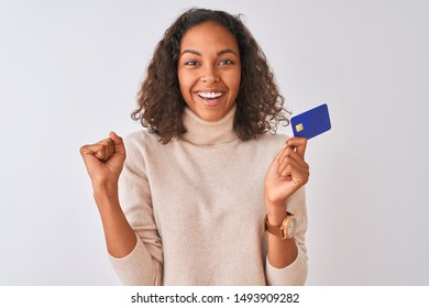 Young brazilian woman holding credit card standing over isolated white background screaming proud and celebrating victory and success very excited, cheering emotion