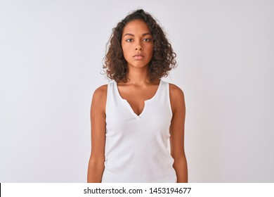 Young brazilian woman wearing casual t-shirt standing over isolated white background with serious expression on face. Simple and natural looking at the camera.
