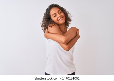 Young brazilian woman wearing casual t-shirt standing over isolated white background Hugging oneself happy and positive, smiling confident. Self love and self care