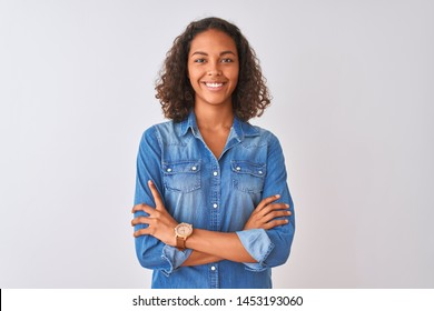 Young brazilian woman wearing denim shirt standing over isolated white background happy face smiling with crossed arms looking at the camera. Positive person.
