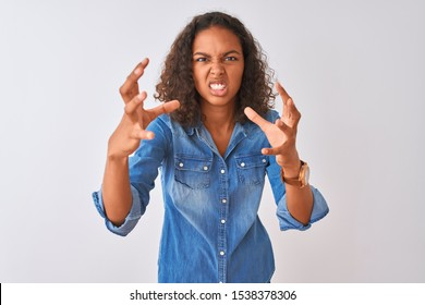 Young brazilian woman wearing denim shirt standing over isolated white background Shouting frustrated with rage, hands trying to strangle, yelling mad