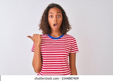 Young brazilian woman wearing red striped t-shirt standing over isolated white background Surprised pointing with hand finger to the side, open mouth amazed expression.
