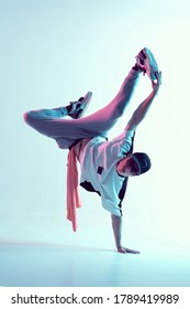 Young breakdancer guy stands on one hand dancing hip-hop in neon light. Dance school poster