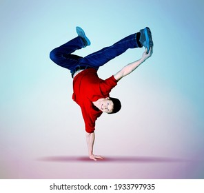Young breakdancer guy stands on one hand dancing and posing