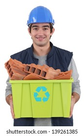 young bricklayer carrying recycling tub full of red bricks