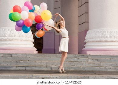 Young bridal with colorful latex balloons keeping her dress, urban scene, outdoors