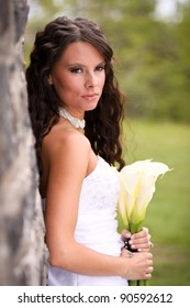 A young bride against an old stone wall holding a bouquet of cream lilies