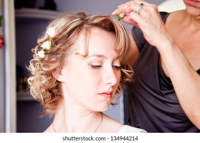 Young bride applying wedding hairstyle by hairstyle artist