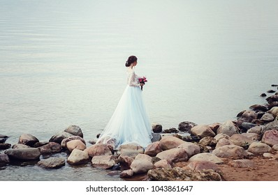 Young bride with bouquet walking along lake coast wearing beautiful wedding dress