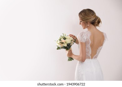 Young bride with elegant hairstyle holding wedding bouquet on white background, back view