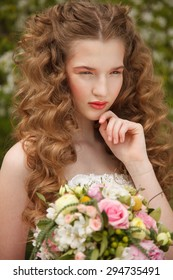 Young bride with flowers stands near  blooming apple tree with colorful posy. Professional style and make-up