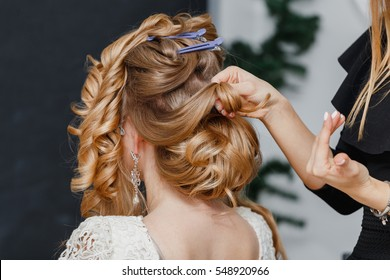Young bride getting her hair done before wedding by professional hair stylist