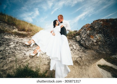 Young  bride and groom are in the nature against the backdrop of large rocks and a beautiful sky. Newlyweds Outdoors