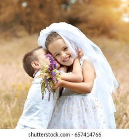 Young bride and groom playing wedding summer outdoor. Children like newlyweds. Little girl in bride whote dress and bridal veil kissing her little boy groom, kids game. Bridal, wedding concept.
