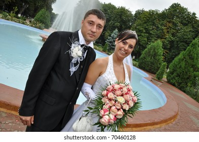 Young bride and groom posing near the pool