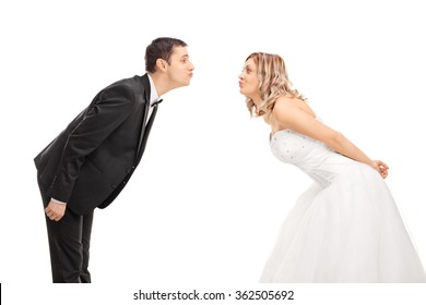 Young bride and groom standing opposite of each other and going in for a kiss isolated on white background