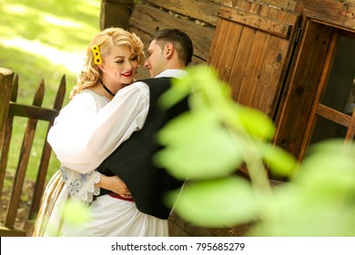 young bride and groom wearing romanian traditional costume.  and smiling at each other in a garden outdoors.