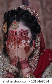 young bride hands on her face showing wedding jewlery, Mehndi on hands and hair style