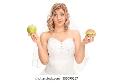 Young bride holding an apple in one hand and a hamburger in the other isolated on white background