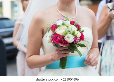 Young bride holding beautiful wedding bouquet in her hands