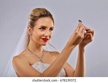 Young Bride holding up and looking at her wedding ring.
