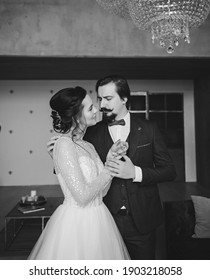 Young bride in lace dress with handsome groom in classic suit. Indoors portrait couple