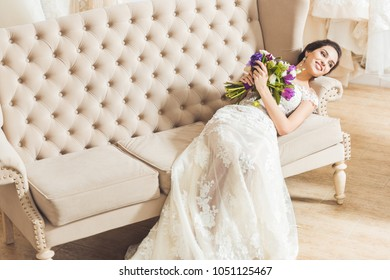 Young bride lying on sofa with flowers bouquet in wedding atelier